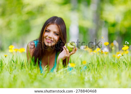 Woman with apple laying on green grass - stock photo