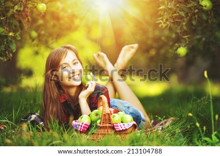 Woman with apples in the garden. Young attractive woman with a full basket of ripe red and green apples is lying on the grass in the apple garden and smiling. Harvest season. Country lifestyle.   - stock photo
