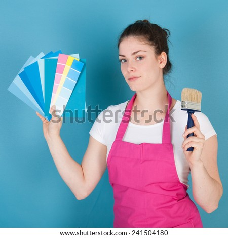 Woman with apron and paint brush against blue wall