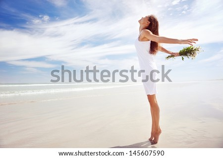 woman with arms out freedom girl on beach with flowers in summer - stock photo