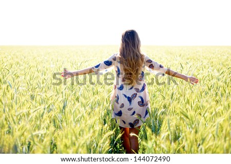 Woman with arms outstretched in wheat field at sunny day - stock photo