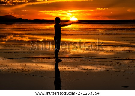 Woman with arms outstretched take sun in his hands. Salares de Uyuni, Bolivia, sunset light, clouds in the horizon reflected in the wet salt surface - stock photo