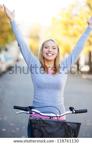 Woman with arms raised while sitting on bike - stock photo