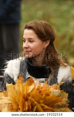 Woman with autumn leafes in city garden.