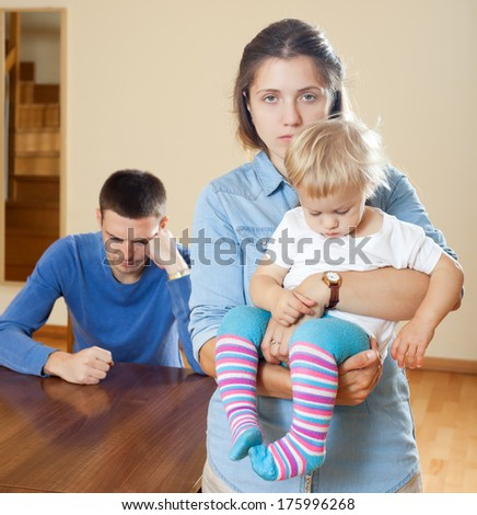 Woman with baby against husband after quarrel at home - stock photo