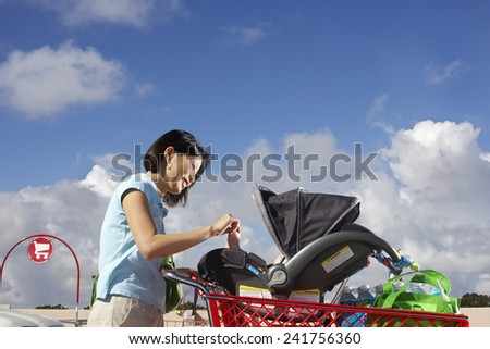 Woman with Baby in Shopping Cart - stock photo