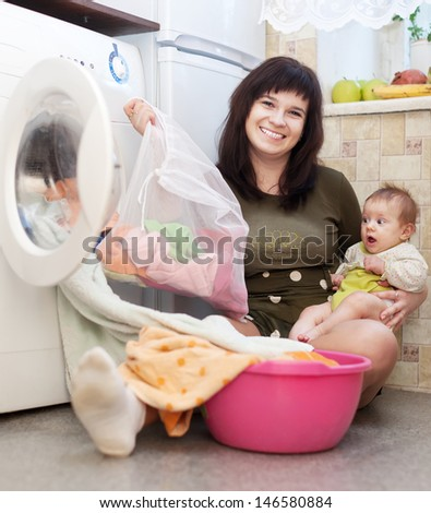 woman with baby putting clothes into washing machine and looking at camera