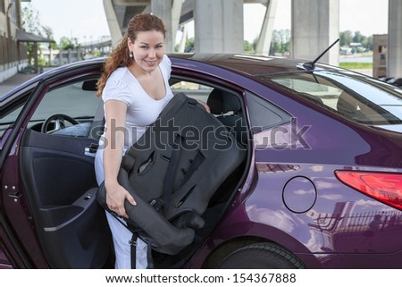 Woman with baby safety seat placing it in the car - stock photo