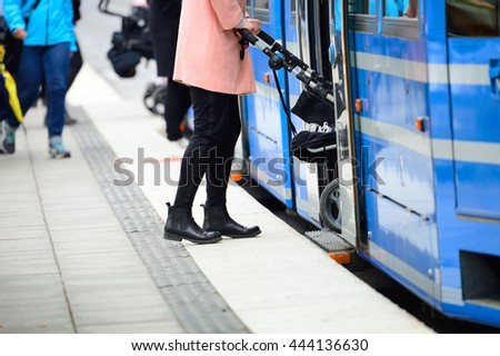 Woman with baby stroller entering tram