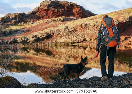 Woman with backpack and pet dog looking over the scenic lake and enjoying the view after a hard hike - stock photo