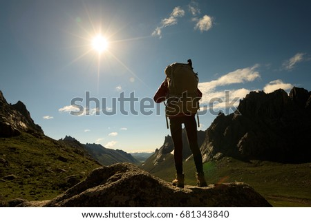 woman with backpack hiking in sunrise mountains