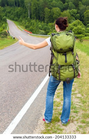 Woman with backpack hitchhiking on a country road