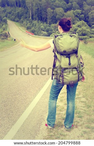 Woman with backpack hitchhiking on a country road. Toned image - stock photo