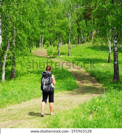 Woman with backpack in a forest. - stock photo