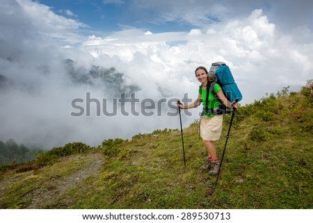 Woman with backpack is hiking in Caucasus mountains in Georga