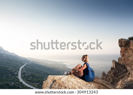 Woman with backpack is on mountain peak and looking at sunrise above the sea
