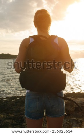 Woman with backpack on the sunset. - stock photo