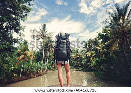 Woman with backpack standing near big tropical river and looking far away - stock photo