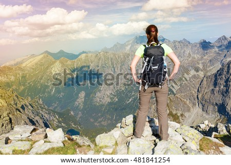 Woman with backpack standing on the edge, looking at mountains