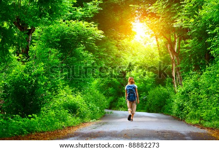 Woman with backpack walking on a wet road among green tropical trees - stock photo