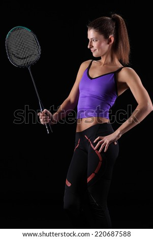 woman with badminton racket isolated on black - stock photo