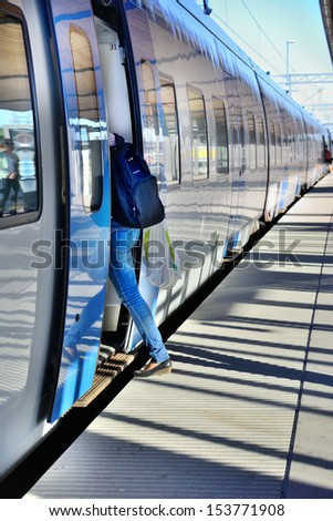 Woman with bag enters train - stock photo