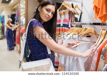 Woman with bag looking through clothes and smiling in shopping mall - stock photo