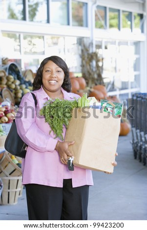 Woman with bag of groceries outside grocery store - stock photo
