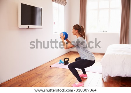 Woman With Ball Working Out To Fitness DVD On TV In Bedroom - stock photo