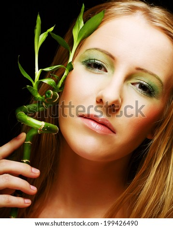 woman with bamboo on black background - stock photo