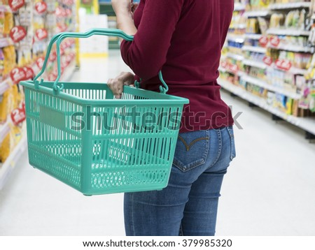 Woman with basket walking in supermarket - stock photo