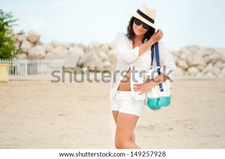 Woman with beach hat relaxing by the ocean at exotic resort - stock photo