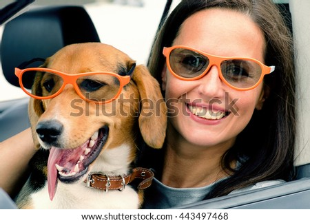 Woman with beagle dog in  car. Summer vacation. Toned