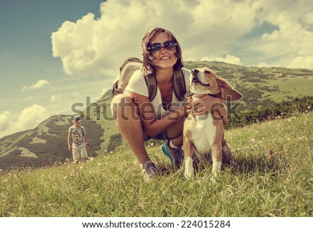 Woman with beagle on mountain hill - stock photo