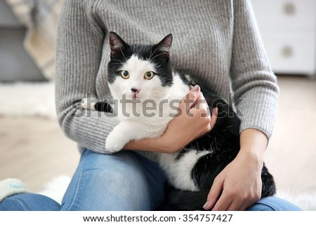 Woman with beautiful cat on carpet, indoor