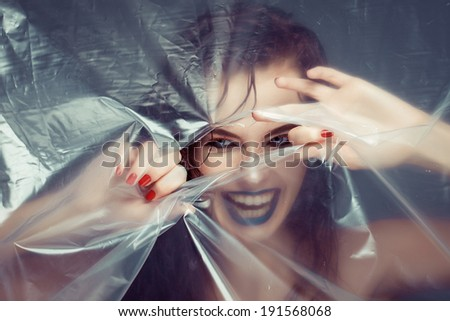 Woman with beautiful eyes and creative eye makeup peering cellophane - stock photo