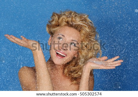 woman with beautiful hair under snow on blue background