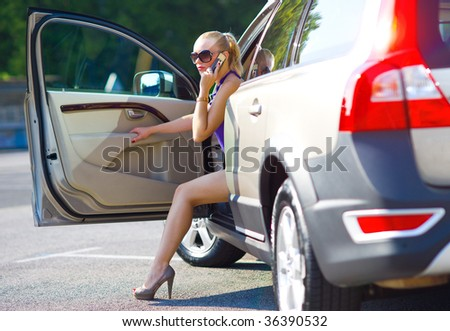 woman with beautiful legs exit the car - stock photo