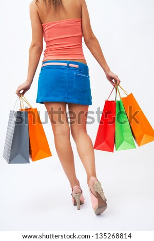 woman with beautiful legs holding shopping bags in hands - stock photo