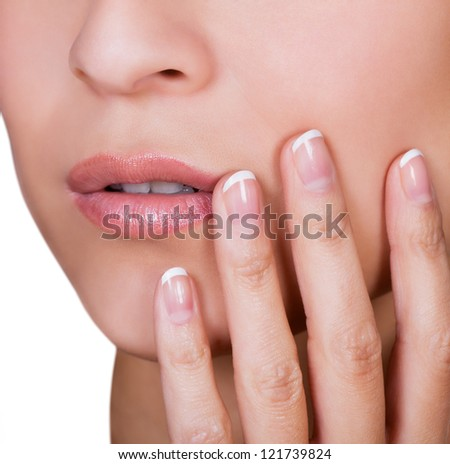 Woman with beautiful manicured finger nails covered in cleared gloss lacquer or nail varnish holding her hand to her cheek - stock photo