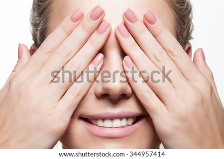 Woman with beautiful natural manicure closes eyes with her hands - stock photo