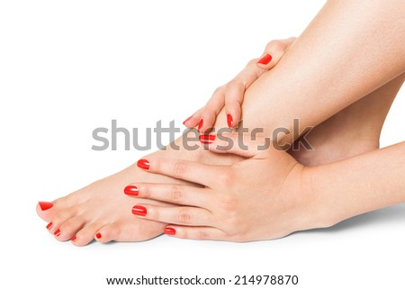 Woman with beautiful neatly manicured red finger and toenails sitting with bare feet clasping her ankles to display her nails, closeup on white in a fashion and beauty concept
