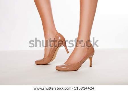 Woman with beautiful smooth sexy legs posing in a pair of classical court shoes in beige leather with high heels - stock photo