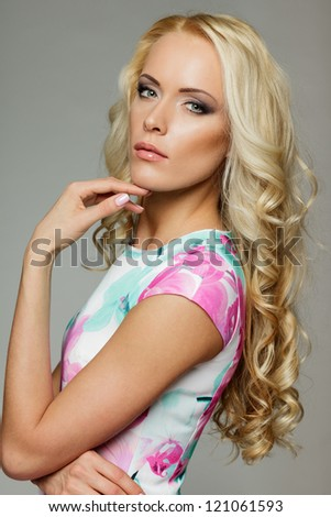Woman with beauty long blond hair posing at studio, over gray background