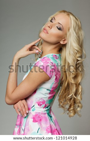 Woman with beauty long blond hair posing with closed eyes, over gray background - stock photo