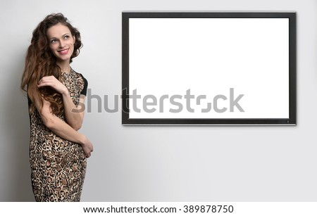 woman with beauty long curly hair and TV hanging on the wall - stock photo
