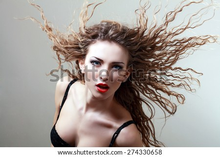 Woman with beauty long natural curly hair - posing at studio.