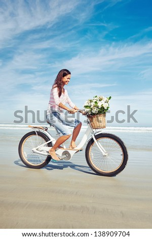 woman with bicycle and flowers in basket smiling carefree and happy - stock photo