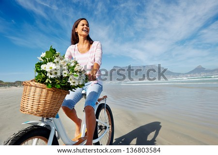 Woman with bicycle on beach in Cape Town, South Africa and Table Mountain - stock photo