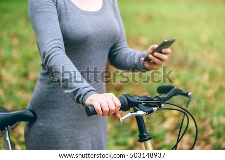 Woman with bicycle using mobile phone in park during autumn season, lifestyle and technology concept, selective focus